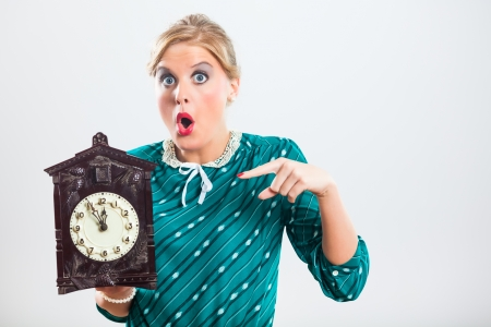Retro woman is holding clock and showing that time is running out very fast  photo