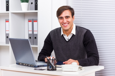 Portrait of young businessman sitting in his office and working  Stock Photo