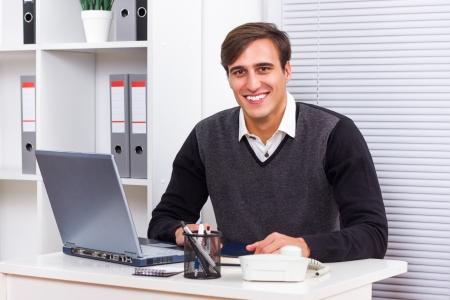 Ritratto di giovane uomo d'affari seduto nel suo ufficio e di lavoro