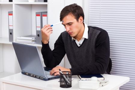 Giovane imprenditore seduto nel suo ufficio, lavorando sul suo computer portatile e pensando a qualcosa Archivio Fotografico