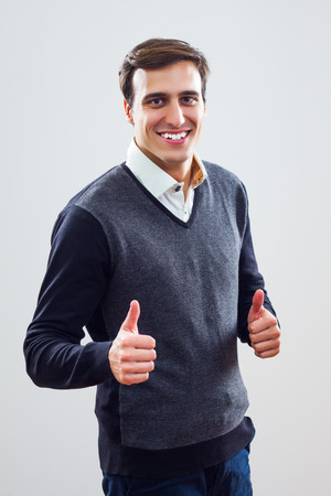 Young businessman giving thumbs up sign  photo