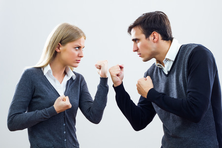 Businesswoman and businessman are very angry at each other and they are fighting  photo