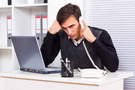 Worried businessman sitting in his office and talking on the phone photo