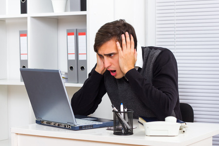 Young businessman is shocked by something he sees on his laptop monitor photo