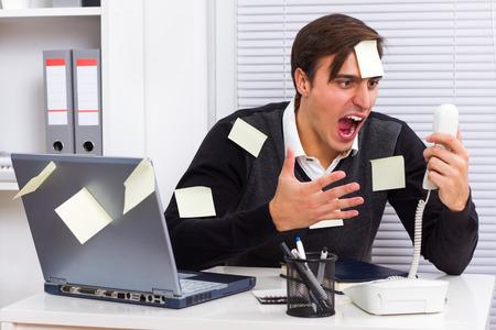 彼のオフィスに電話で叫んでいる実業家 写真素材
