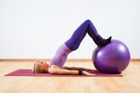 relaxation exercise: Young women  doing  pilates  exercises with fitness ball