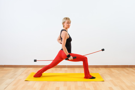Young woman exercising with body bar