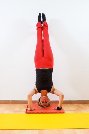 Yoga-Sirsasana Crane pose with both legs up photo