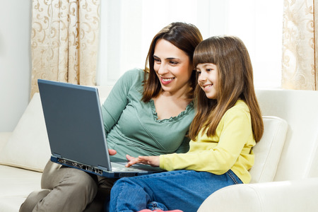 parents with one child: Mother and daughter sitting on sofa at their home using laptop together