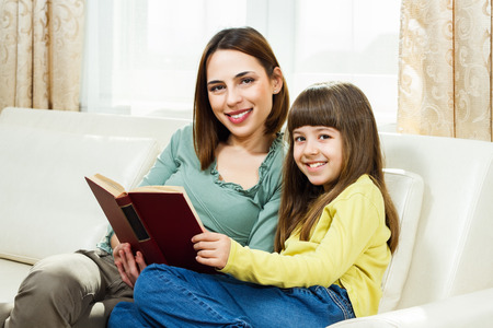 母と娘、自宅でソファに座って、一緒に本を読んで 写真素材