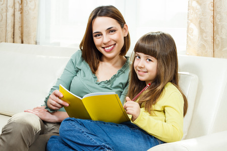 Mother helps daughter with her homework at their home  Stock Photo