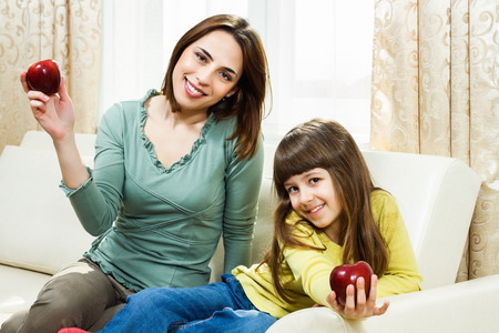 Mother and daughter sitting on sofa at their home and showing apple,they are having healthy snack  photo