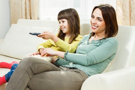 madre soltera: Madre e hija sentada en el sof� en su casa, comiendo palomitas y viendo la televisi�n