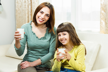 Mother and daughter sitting on sofa at their home and holding glass of milk  photo