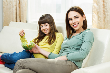 30 34 years: Mother is feeding her little daughter with vegetables  Stock Photo