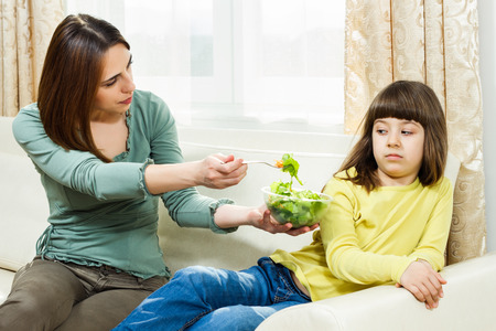 Mother is giving vegetables to her daughter to eat but she is very angry,she don t like it