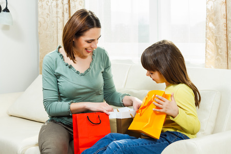 Madre e figlia seduta sul divano a casa loro e guardare cosa hanno comprato