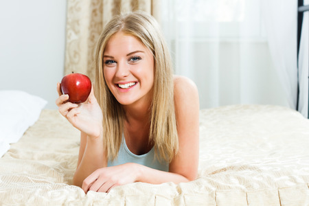 Young woman  is lying on her bed and showing apple  photo