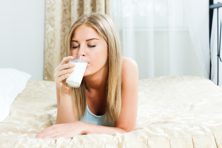 Young woman is lying on her bed and drinking milk  photo