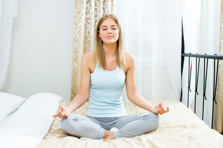 Beautiful blonde woman is meditating on bed in her bedroom  photo