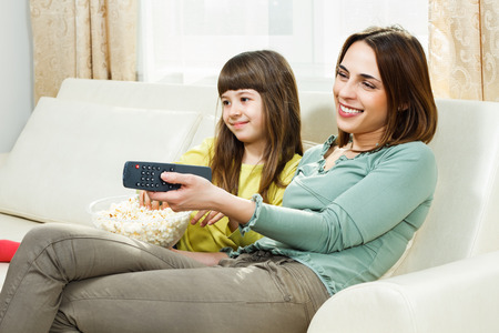 Mother and daughter sitting on sofa at their home,eating popcorn and watching tv  Stock Photo