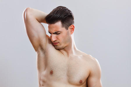 young man smelling his armpit  photo