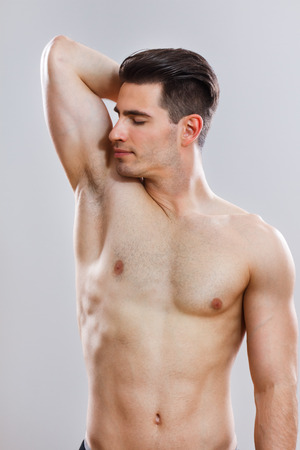 armpit hair: handsome young man smelling his armpit after shower  Stock Photo