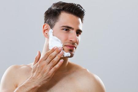 Ritratto di uomo bello applicare la crema da barba sul viso Archivio Fotografico