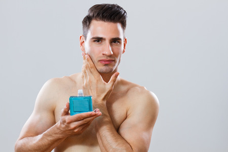 handsome man applying aftershave  photo