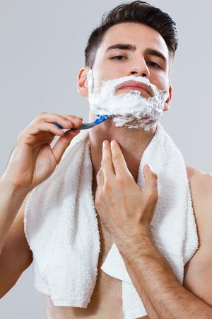 ハンサムな男彼のひげを剃る