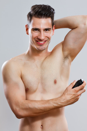 handsome man using deodorant   photo