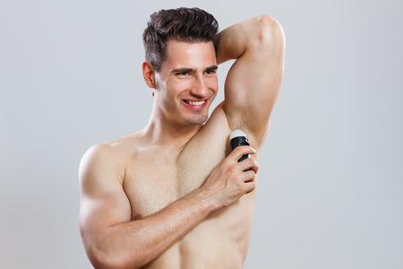 Photo of handsome man applying antiperspirant   photo