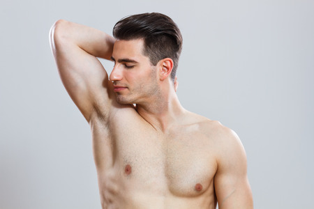 handsome young man smelling his armpit after shower  photo