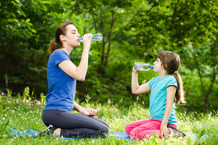 girl drinking water: Mother and daughter drinking water after exercise