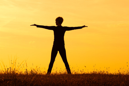 Photo of a woman with her arms outstretched looking at sunset   photo