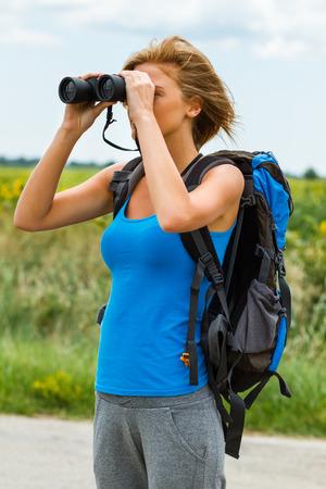女性は、国の道路上に立っていると双眼鏡を通して何かを見ています。