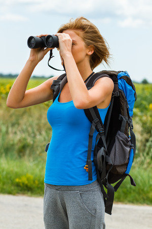 Woman is standing on the country road and watching something through binoculars . Stock Photo