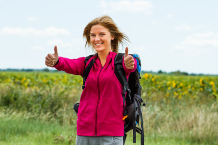 Cheerful blonde woman with backpack is ready for hiking  and she is showing thumbs up.