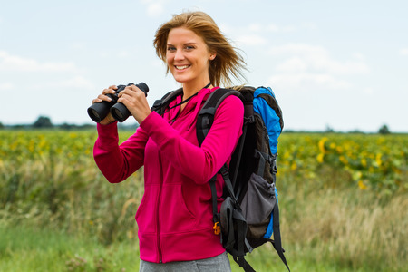 Cheerful blonde woman is standing in the nature and holding binoculars . Stock Photo