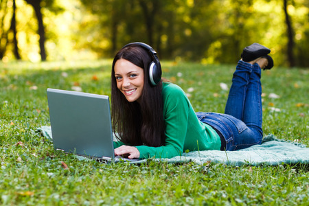 Laptop, Women, Headphones, Using Laptop, Listening, Netbook, Nature, Technology, Green, Happiness, Enjoyment, Relaxation, Connection, One Person, Caucasian, Lifestyles, Outdoors, Looking At Camera, Internet, Park, Meadow, Spring, Autumn, Brown Hair, Che photo