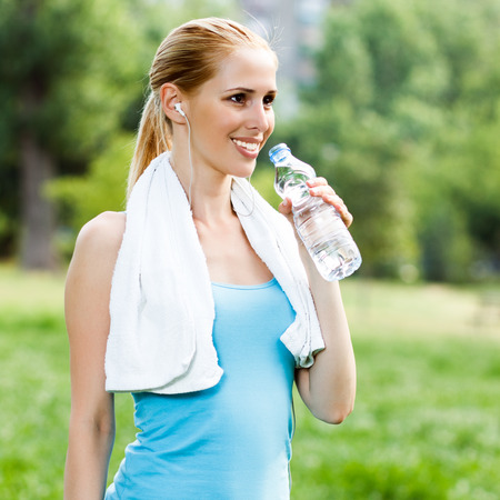 Woman is standing in the park and drinking water after exercise.