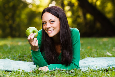 Young woman is eating apple while lying down in nature. photo