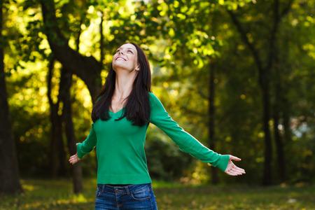 自然の中に美しい若い女性が楽しんでいます。 写真素材