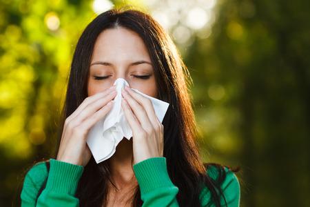 sneezing: Woman is sneezing into handkerchief. Stock Photo