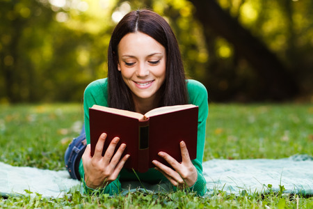 Young beautiful woman is reading a book and enjoy in her free time. Stock Photo