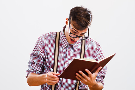 Nerdy man is surprised because of something he had read in a book.