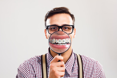 Nerdy man is holding loupe and showing his teeth with braces. Stock Photo