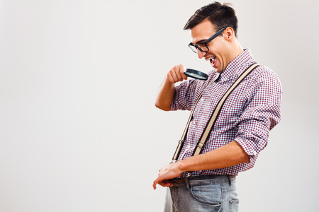 Funny nerdy guy is peeking in his paints with loupe, his macho problems are seems to be over.