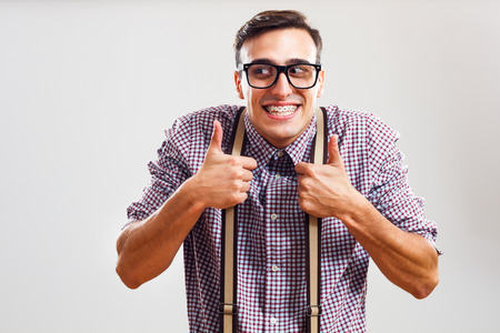 grimacing: Happy nerdy man is showing thumbs up.