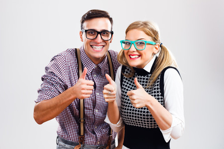 Happy nerdy couple showing thumbs up. Stockfoto